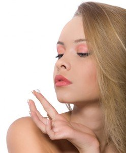 Beautiful blond woman with cream for skin care on her finger